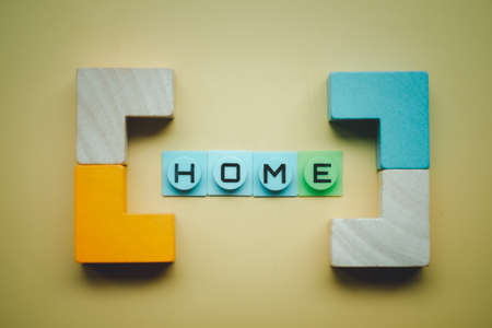 HOME text in bracket make from wood block on a yellow background. Property investment, home mortgage,