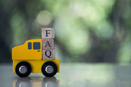 The abbreviation FAQ on wooden cubes placed on wood car against nature background.