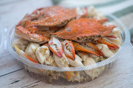 Steamed horse crab claws in circle box on wooden board background. Ready to eat. Top view.