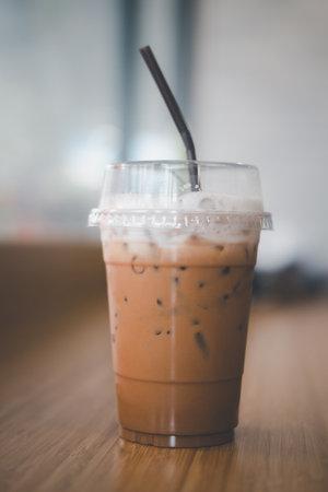 Iced coffee Mocha with straw on wood table 免版税图像