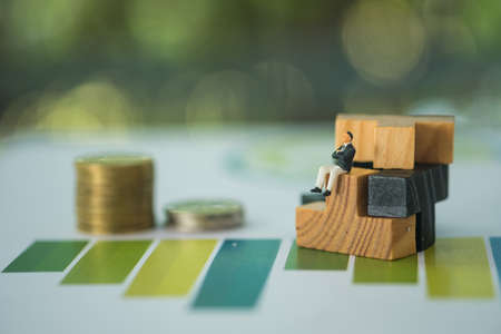 Business people sitting on wood puzzle pieces with stock of coin on graph. Image use for business concept.
