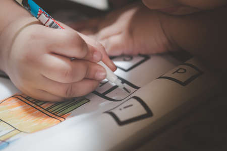 Little boy write to paper with pencil on desk. The concept of practice writing