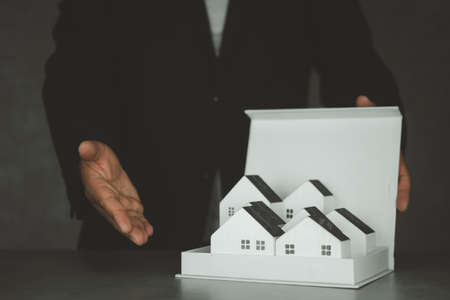 Man in suit realtor offer many home for customer. Realtor selling real estate property. buying renting home concept 免版税图像