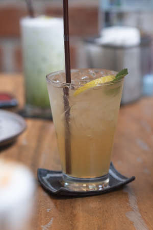 Lemonade with ice and lemon in glass on wood table 免版税图像
