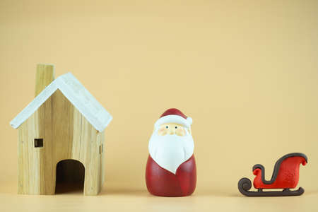 Wood home, cute Santa claus and sleigh. Christmas figurine against yellow background