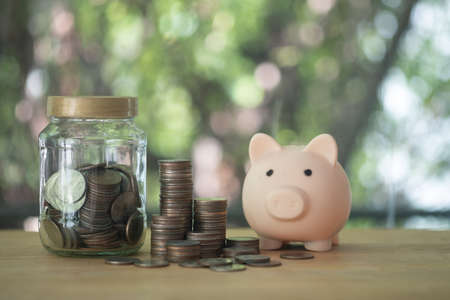 A loaded bottle full of coins and stacking coins pile and cute pink piggy bank for savings with money and planning step up to growing, Saving money for retirement fund and the future plan concept. 免版税图像