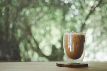 Iced mocha coffee in a double-walled glass on wood table 免版税图像