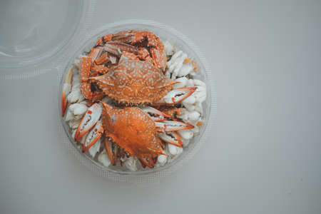 Steamed crab meat in circle box on wooden board background. Ready to eat. Top view.