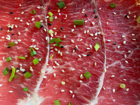 Slice thin raw beef sprinkle black sesame seeds and white sesame seeds with sliced spring onions
