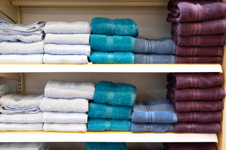 Colorful towels are placed on the shelves for customers at a mall.