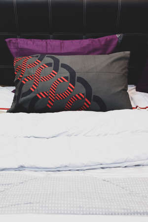 Combination of gray and violet pillows on a bed with white linen in home 免版税图像