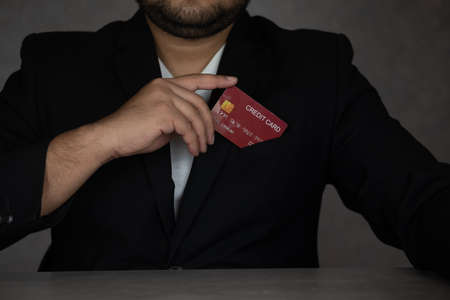 Business man in black suit put or take out credit card in pocket. Businessman with a credit card.