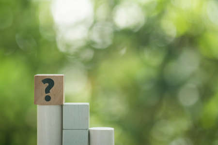 Question mark sign on wood cube on nature background. The concept of support or questionnaire
