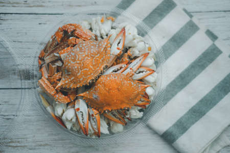 Steamed blue crab legs in circle box on wooden board background. Ready to eat. Top view. 免版税图像