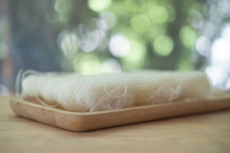 Uncooked white rice noodles on wood tray