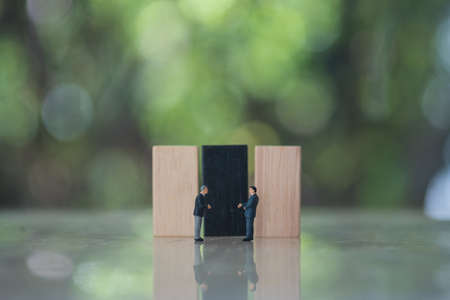 Miniature businessman shaking hands with wooden domino against nature background