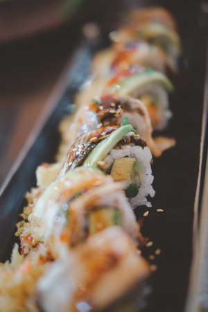 Selective focus of maki roll sushi on long dish
