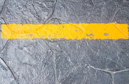 Yellow line painting on the black stone ground
