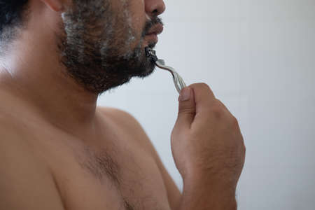 Handsome young man with shaving in bathroom