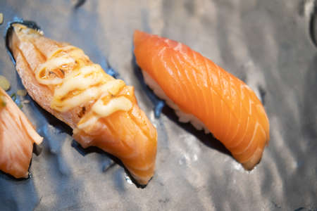 Burnt salmon sushi with mayoungnes sauce and fresh salmon sushi served on plate in Japanese restaurant.