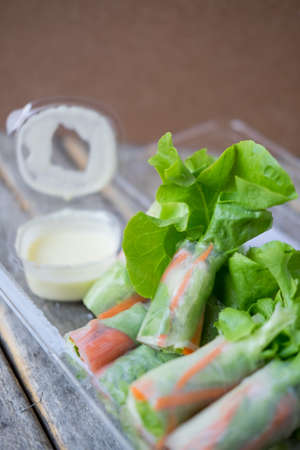 Fresh salad rolls made from lettuce, carrot, cucumber and green oaks wrapped with noodle, served with salad dressing