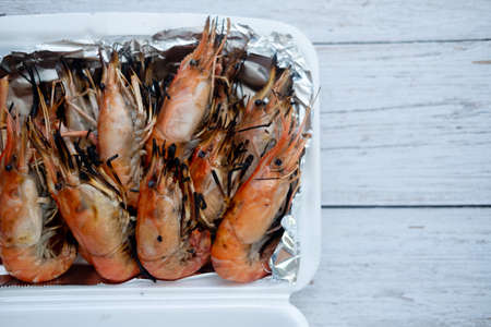 Above view of Thai grilled prawns (shrimps) in the shell placed foam box that wrap with foil paper.
