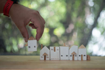 Close up of hand choosing wood house from a row model on wood table. Mortgage and real estate property investment