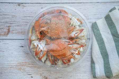 Steamed crab meat pack in circle plastic box for delivery on wood table. Seafood ready to eat delivery business