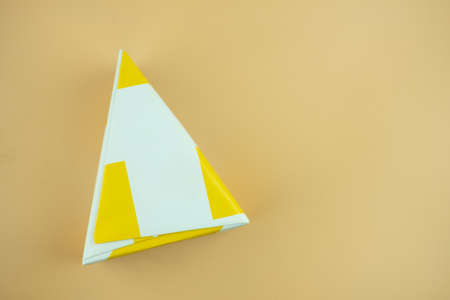 Triangle shape gift box on a yellow background