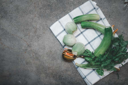 A table arrangement of cucumber, eggplant and cilantro sorted with cutlery. Ready vegetable side dish served