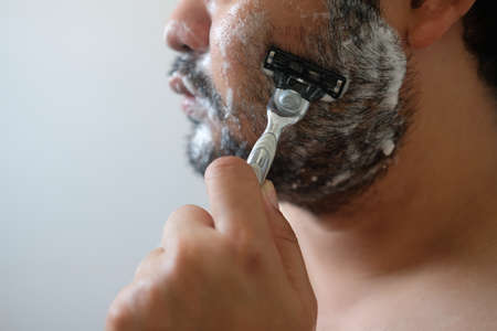 Cropped shot of Asian man is shaving his beard in bathroom