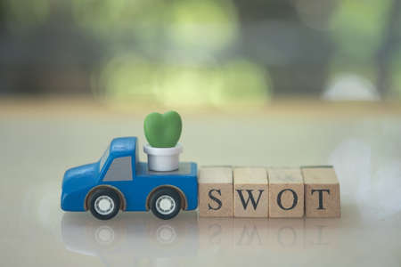 Miniature cactus placed on truck wood toy car with wood block of SWOT. SWOT acronym of strength, weakness, opportunity, and threat
