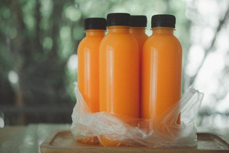 Many orange juice bottles in plastic bag. The concept of delivery drink