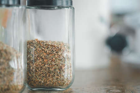 Dried oregano in a glass jar on table in a pizza place 免版税图像