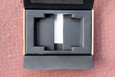 Cardboard open box with empty black compartment