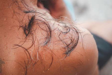 Hair on man's shoulders after haircut at barbershop