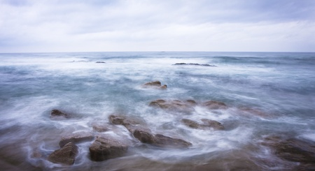 storming: Waterscape of waves bashing onto seaside rocks