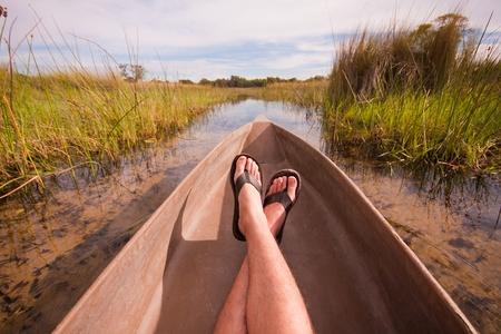 mans voeten ontspannen een kano met een interessant gezichtspunt Stockfoto