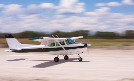 convey: Small airplane landing on a gravel air strip with motion blur to convey movement Stock Photo