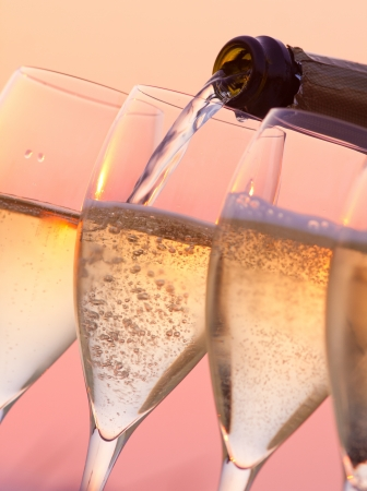Champagne pouring into glasses with a sunset background