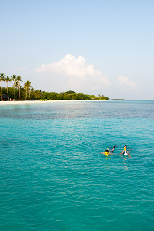 Caucasian couple of tourists snorkel in crystal turquoise water near Maldives Island Stock Photo