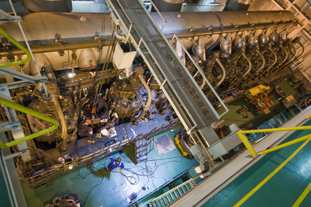 Engineers working on large engine of a ship