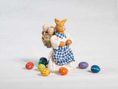 Figurine of woman Easter bunny with basket on her back and colorful easter eggs