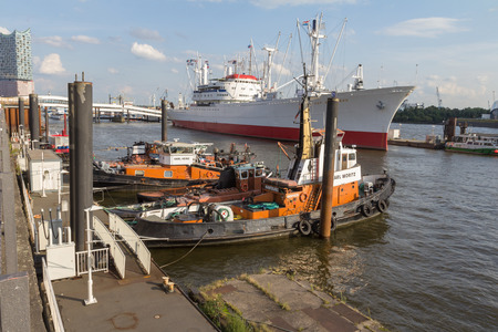 tugboats and a cargo ship in the port of hamburg Editorial