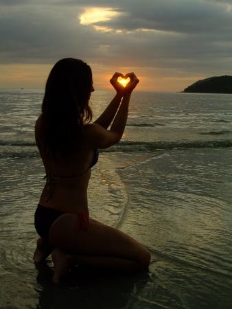 forme: Silhouette de jeune femme faisant forme de coeur avec ses mains au coucher du soleil, modèle sorti