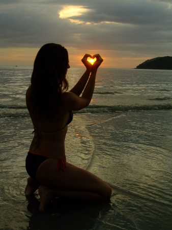 Silhouette of young woman making heart shape with her hands at sunset, model released photo