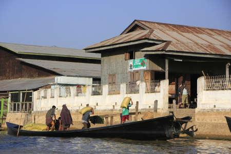Burmese man unloading sacks from a boat, Inle lake, Shan state, Myanmar, Southeast Asia Stock Photo - 14582058