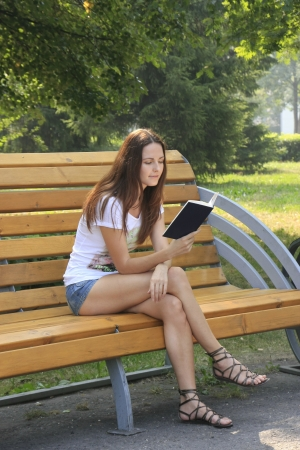 Young woman sitting on a bench reading a book in a park