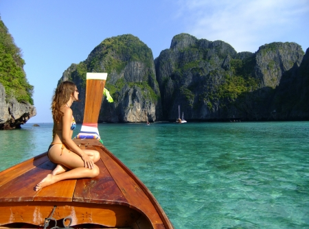 stern: Young woman in bikini sitting on a stern of longtail boat, Phi Phi Lei island, Thailand Stock Photo