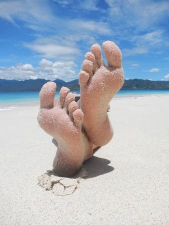 sandy: Pies de arena en una playa tropical
